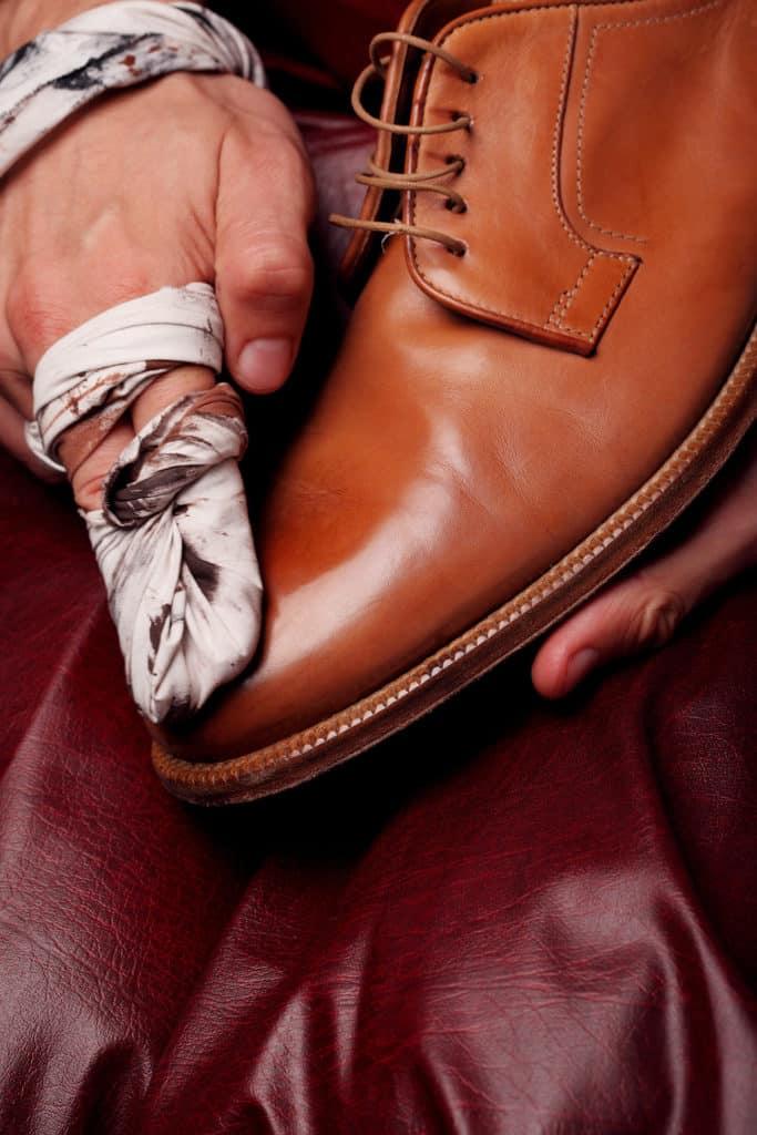 Nella foto un Calzolaio lucida una scarpa in pelle